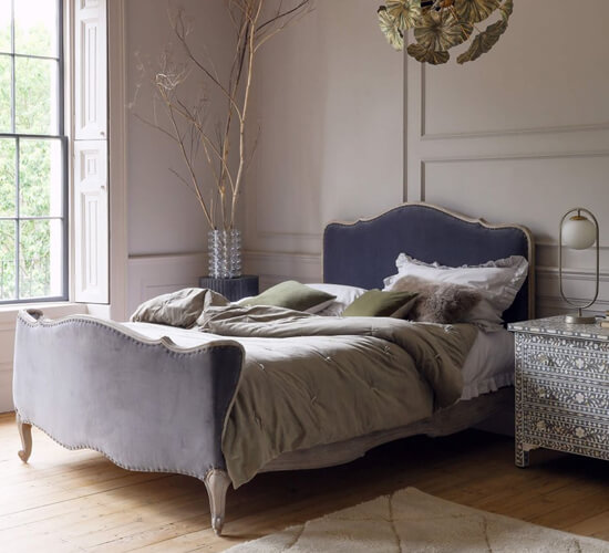 A luxurious bed with a headboard upholstered in grey velvet in a bedroom with a mother-of-pearl bedside table and a hanging pendant lamp