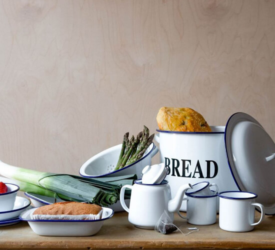 A table with leeks, bread and strawberries arranged in some enamel dishes